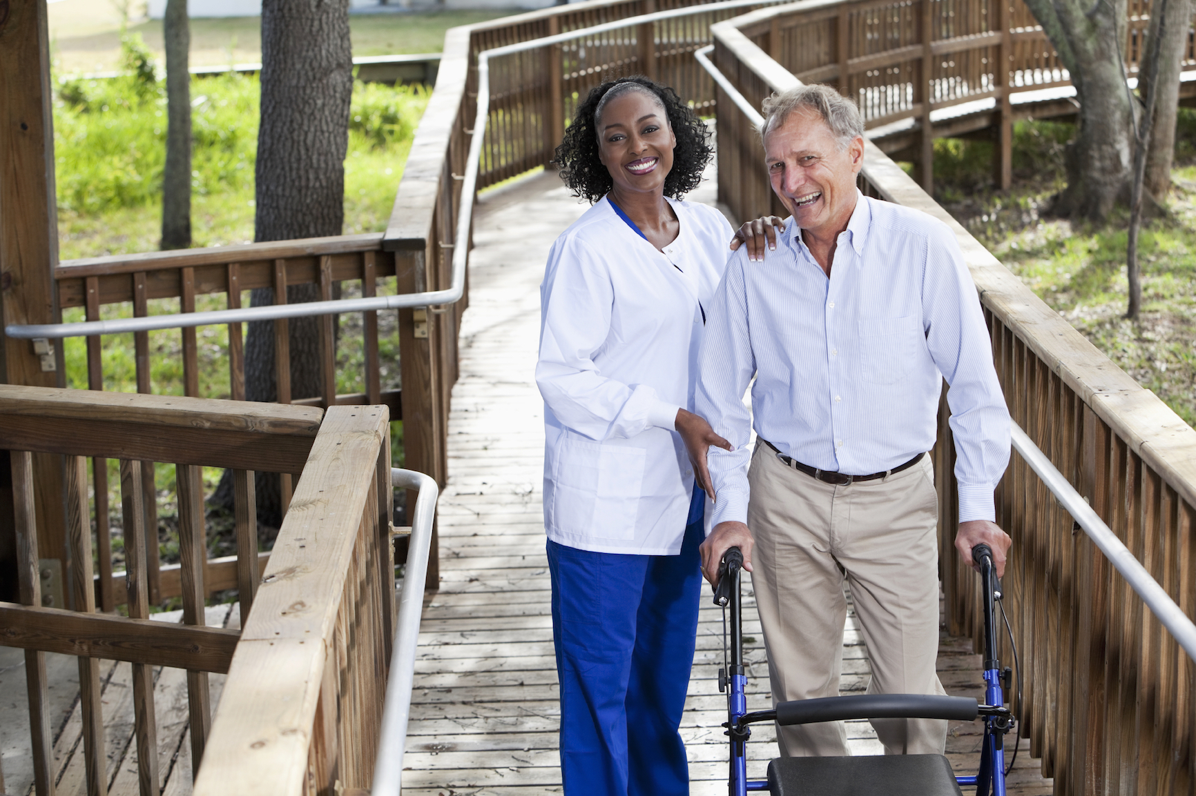 Nurse with senior man on wooden walkway